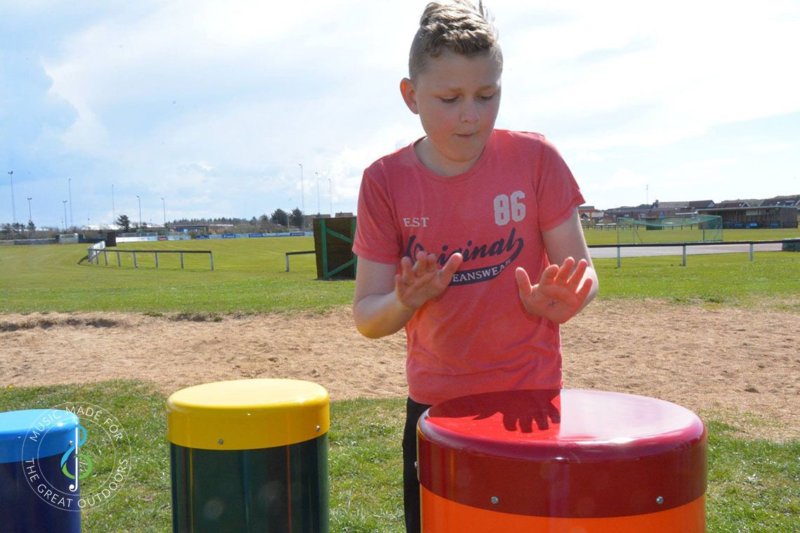 boy splaying outdoor drums with his hands in school playground
