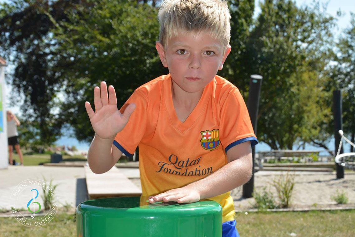 boy playing colourful outdoor drum in playground
