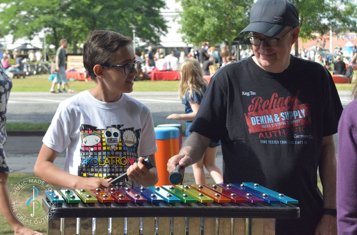 Man and Boy Playing Rainbow Coloured Outdoor Xylophone in Park