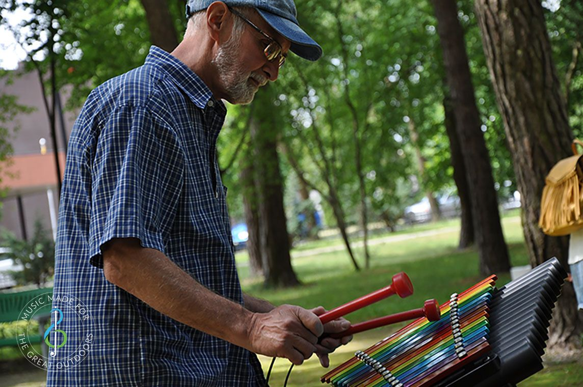 Older Man Playing Colourful Outdoor Xylophone in Park