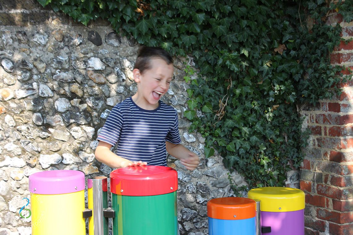 Boy laughing playing on two pairs of colourful outdoor conga drums