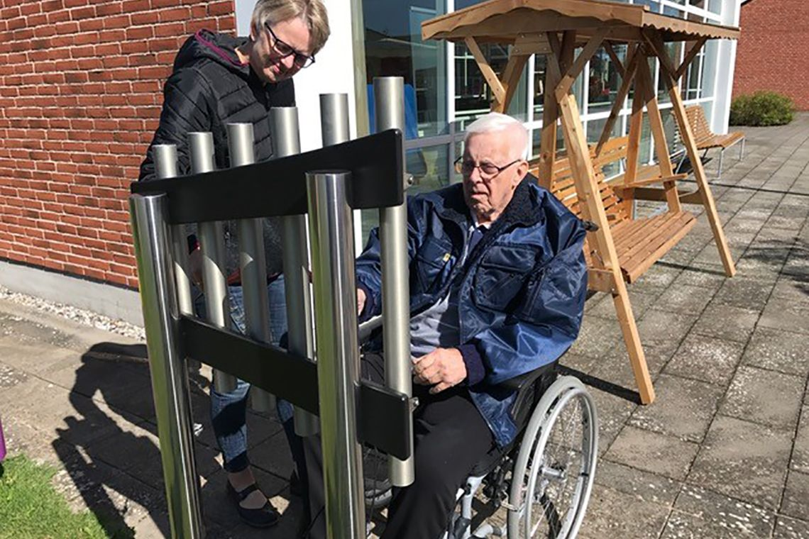 older man in a wheelchair playing an outdoor musical instrument in care home garden