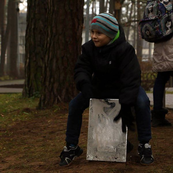 Little boy wearing a winter hat playing a large silver musical instrument in a park