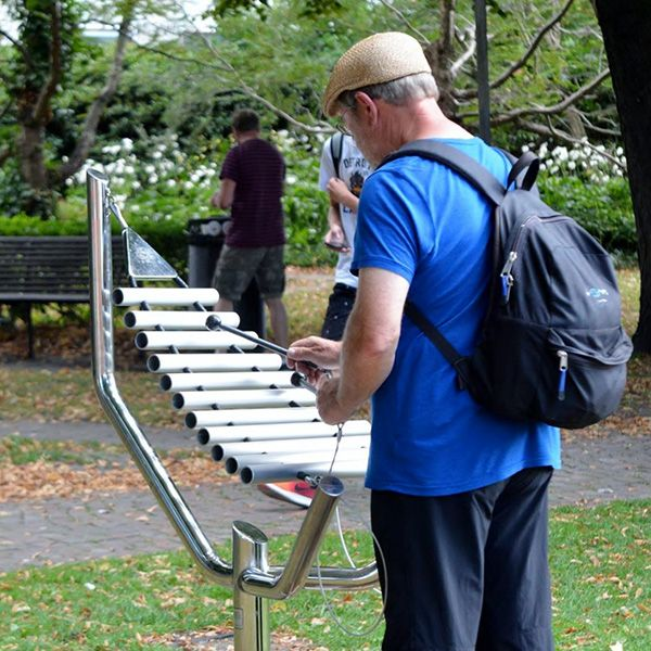 man in a park playing a large metal outdoor xylophone