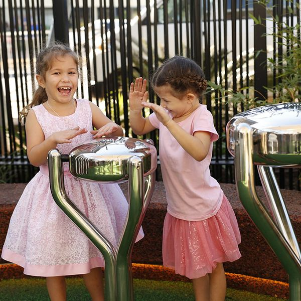 two little girls playing stainless steel tongue drums in shopping precinct playground