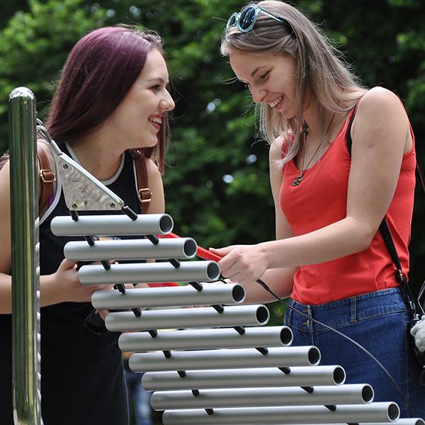Two young ladies laughing and playing a large metal xylophone in a park