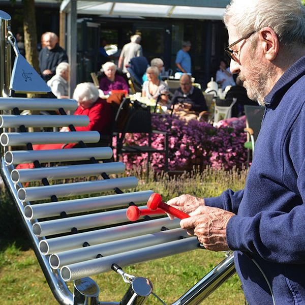 Older man playing an outdoor xylophone in care gome garden
