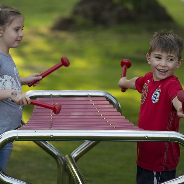boy and girl playing a large outdoor xylophone in a park