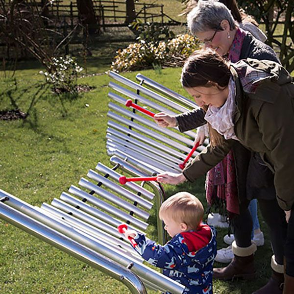 Family playing a large butterfly shaped metallophone in a park