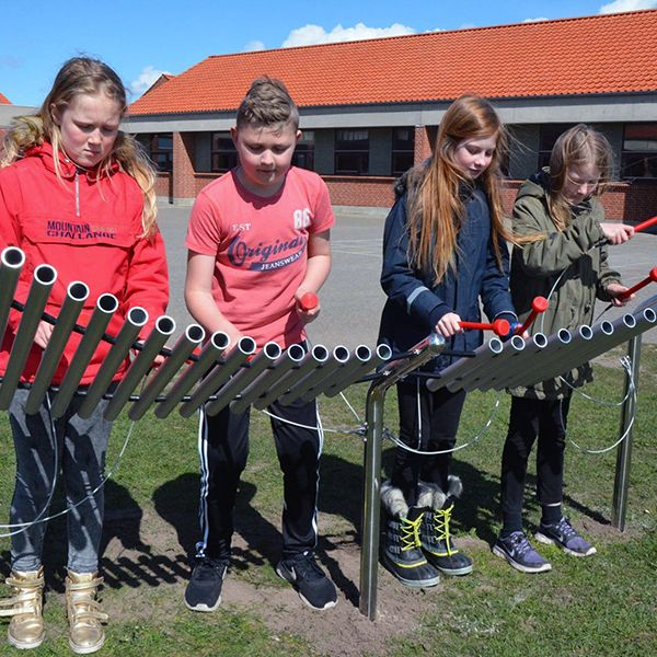 school friends playing a large metallophone in the playground