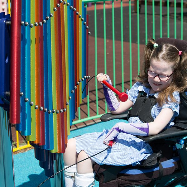 young boy with special needs playing colourful musical chimes in the playground