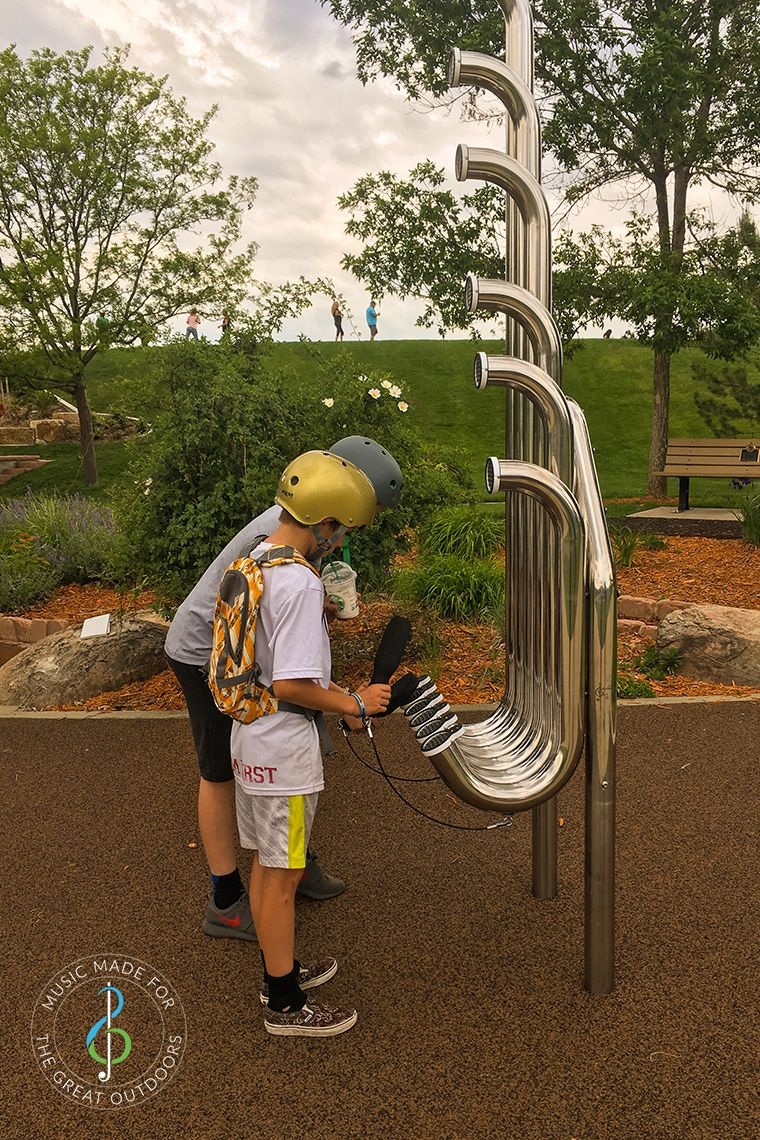 two skater boys in helmets hitting large silver outdoor aerophones or slap tubes in playground