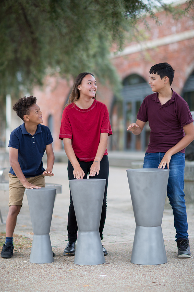 three older children playing three outdoor djembe drums with their hands in a street location