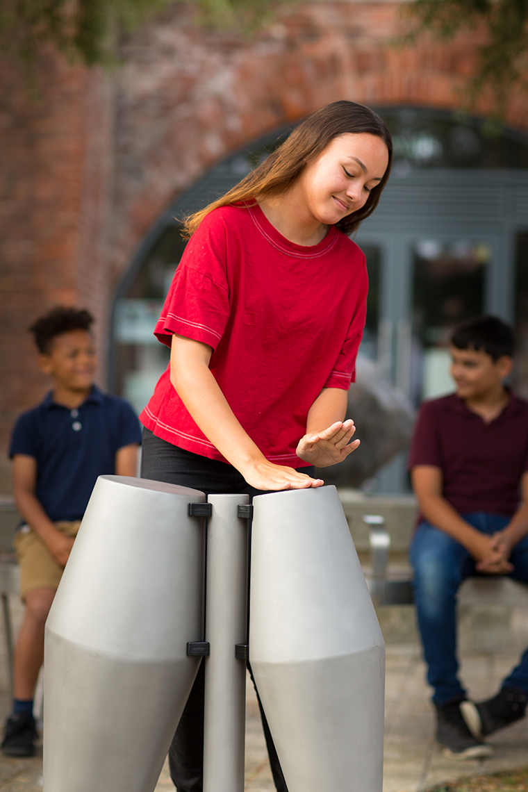 a young black girl in a red t shirt is playing a pair of steel tumbadora drums in a street watched by her two brothers