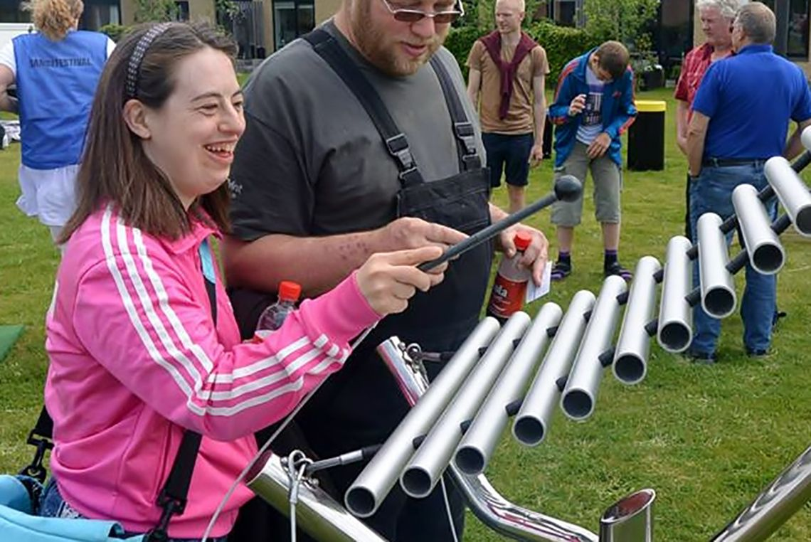 girl with special needs playing a large outdoor xylophone