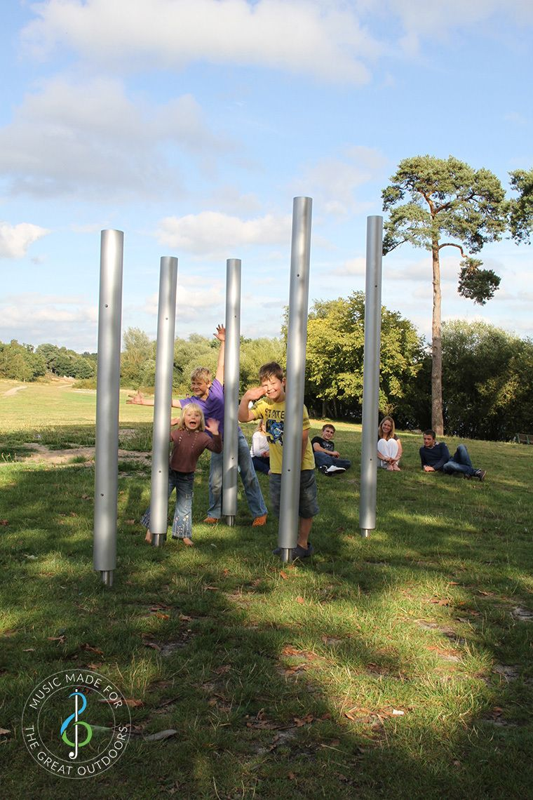Family playing on five large outdoor chimes together in the park