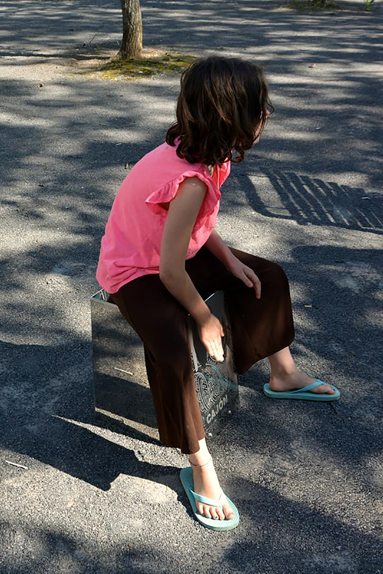 a young girl sitting on a metal outdoor cajon drum designed for musical parks and playgrounds