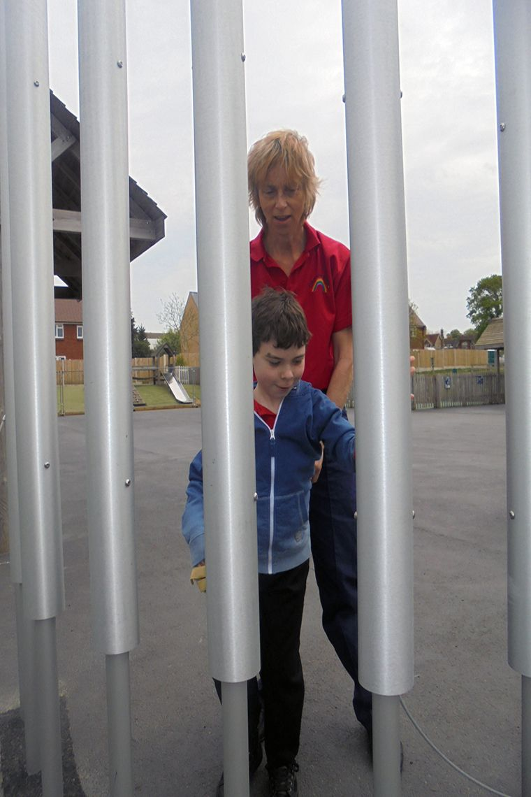 boys with special needs being encouraged to play large playground chimes by his carer