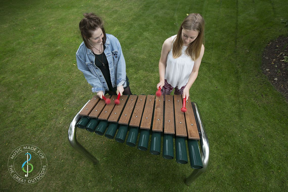 looking down on two teenage girls playing large outdoor marimba with wooden notes in park
