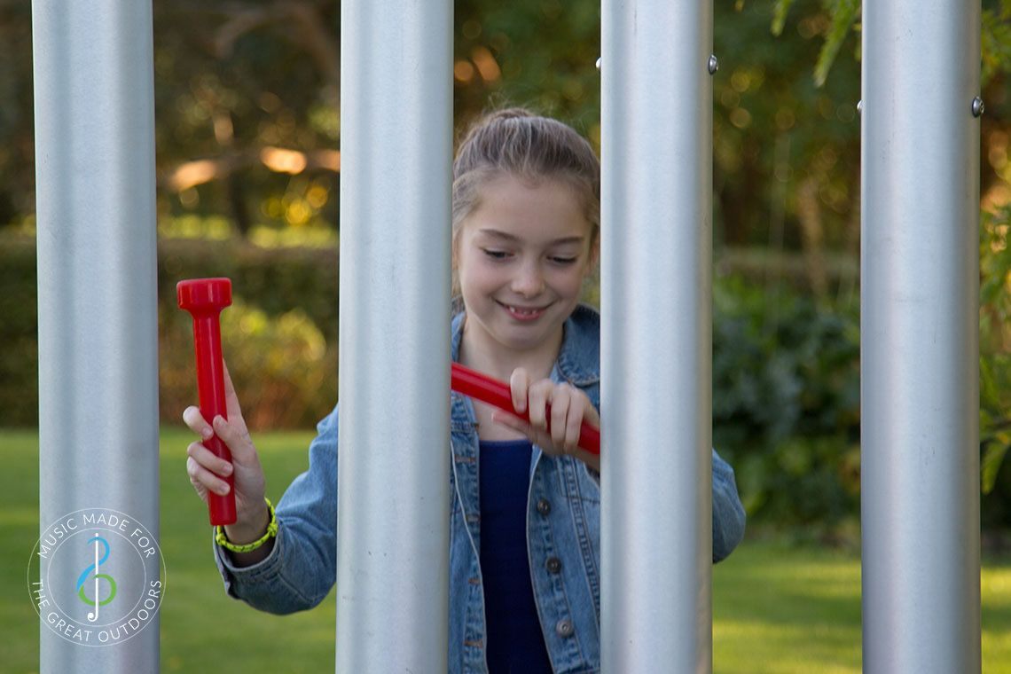 Teenage Girl hitting large outdoor chimes with red beaters in playground