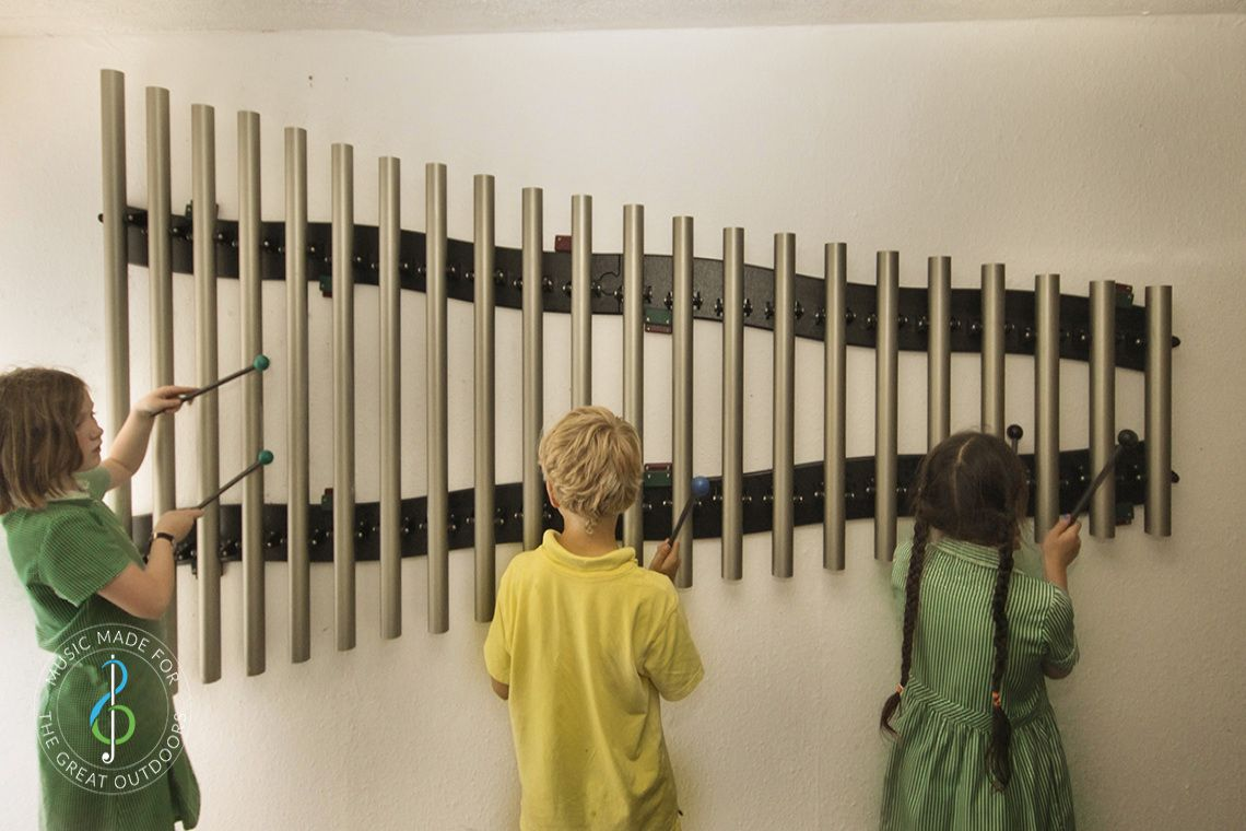three schoolchildren playing on a set of 22 wall mounted chimes