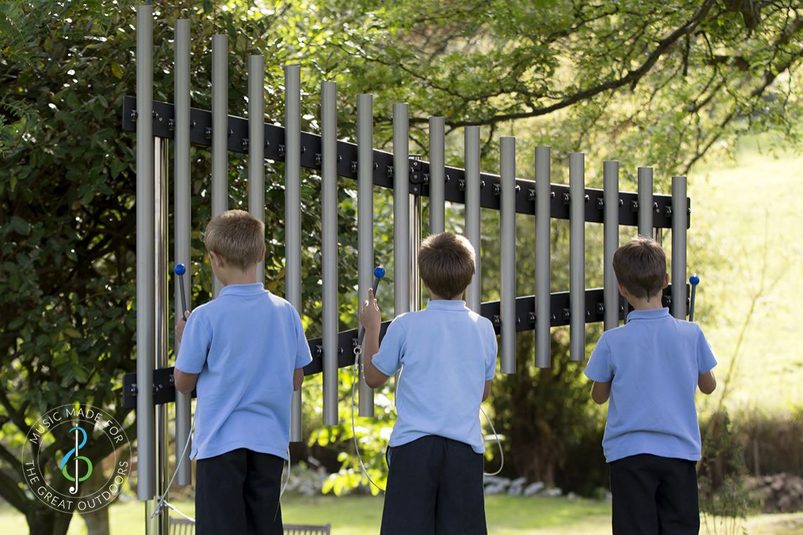 three schoolboys in blue uniform playing on outdoor musical chimes in playground