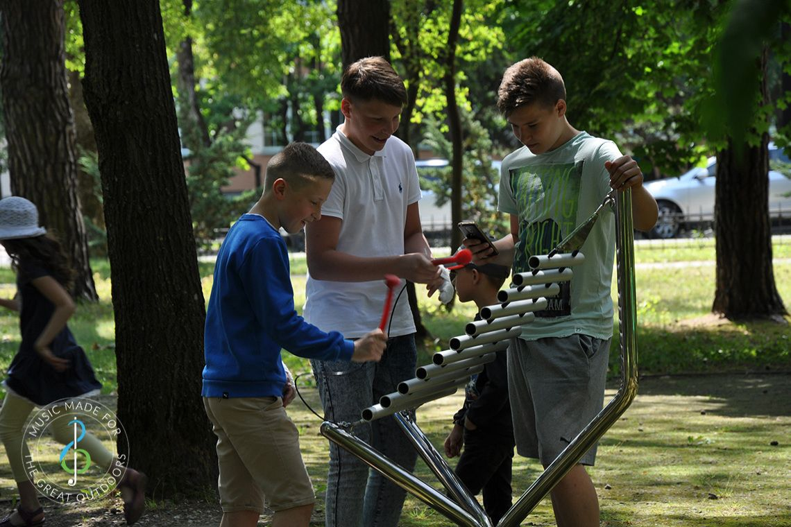 three teenage boys playing a large vertical xylophone made of metal in playground