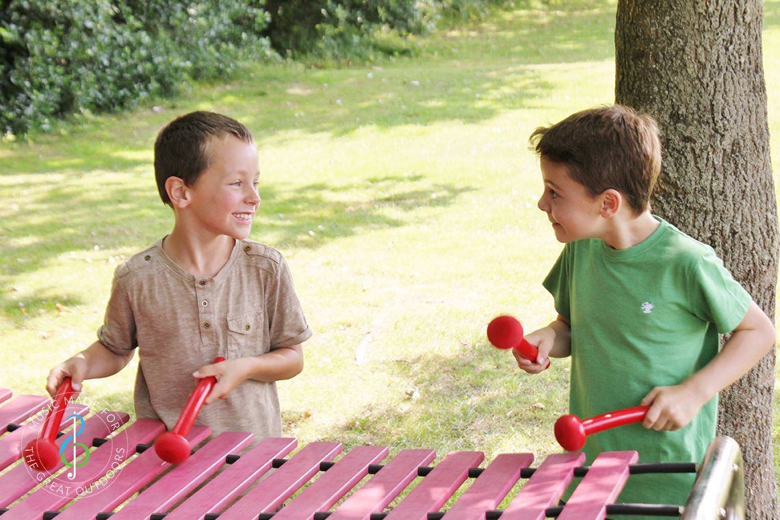 two boys laughing and playing a large outdoor marimba xylophone in a play park