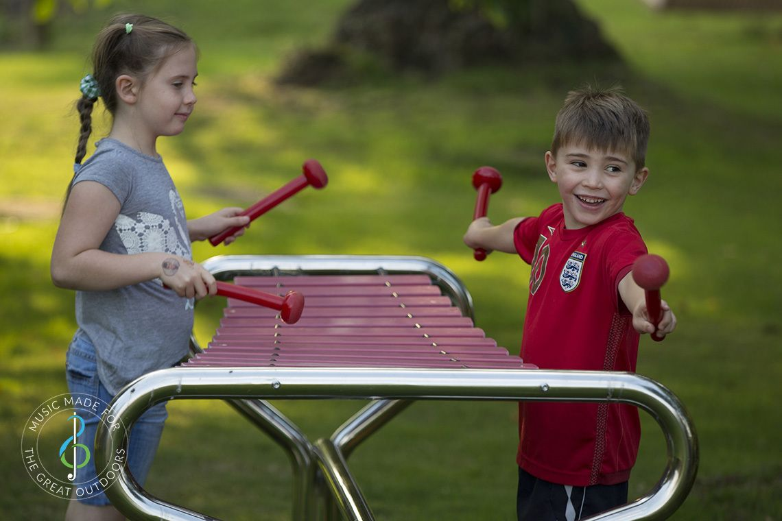 Boy and girl standing on opposite sides and playing a large outdoor marimba xylophone with red beaters