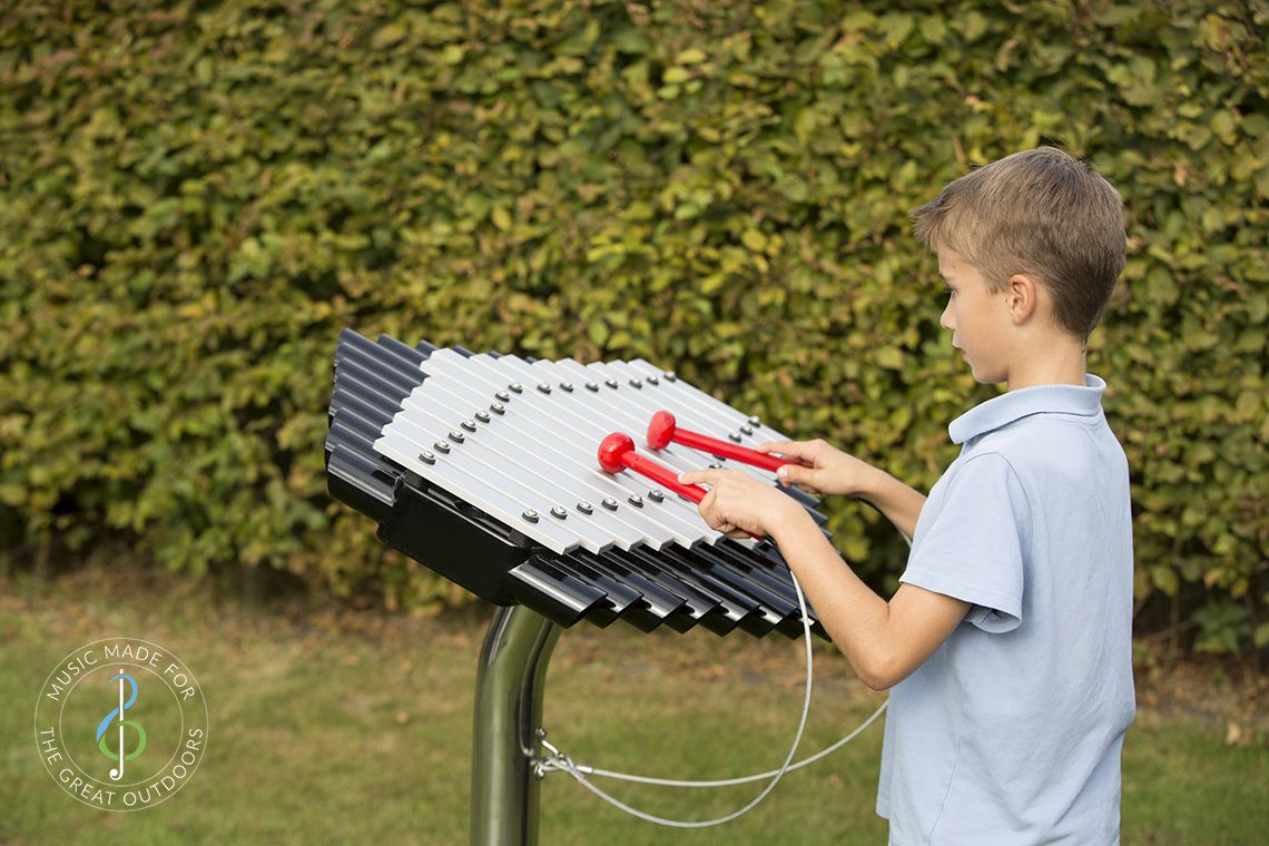 schoolboy in park playing outdoor musical xylophone with silver notes and black resonators