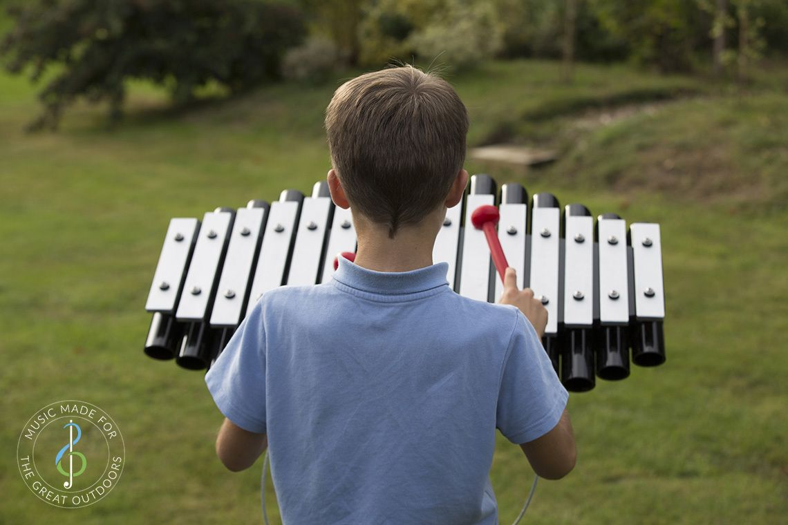 back of boy playing outdoor xylophone with silver notes and black resonators