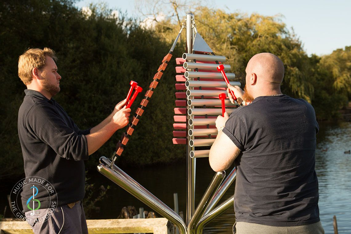 large outdoor musical instrument with one stainless steel post in ground with three vertical xylophones being played by two men