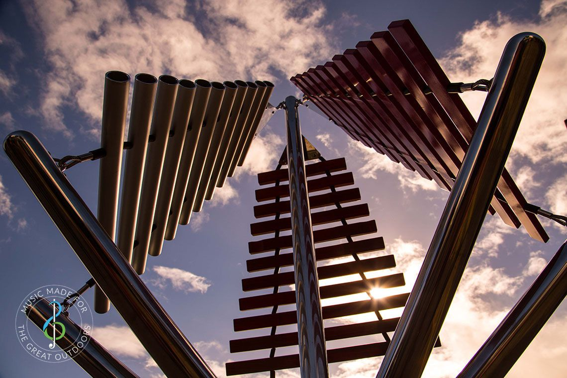 looking up from the ground at a large outdoor musical instrument with one stainless steel post in ground with three vertical xylophones attached