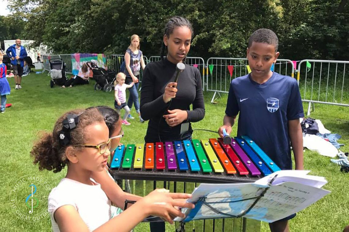 Children Playing Rainbow Coloured Outdoor Xylophone in Park