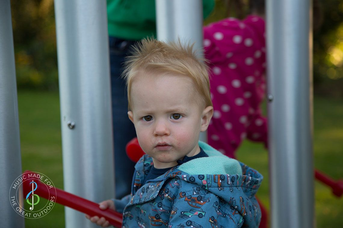 Close up of red haired baby boy hitting huge silver outdoor chimes with a red beater
