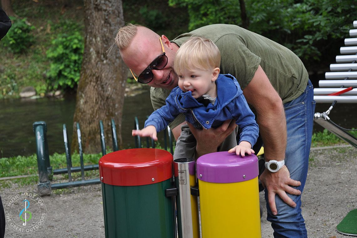 Toddler being held up by his father to play on colourful outdoor conga drums in park