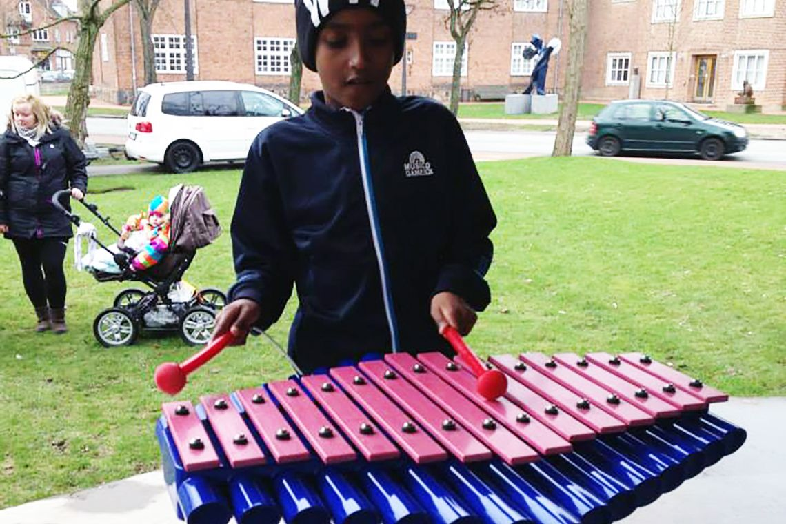 young boy playing a blue and pink xylophone in a playground