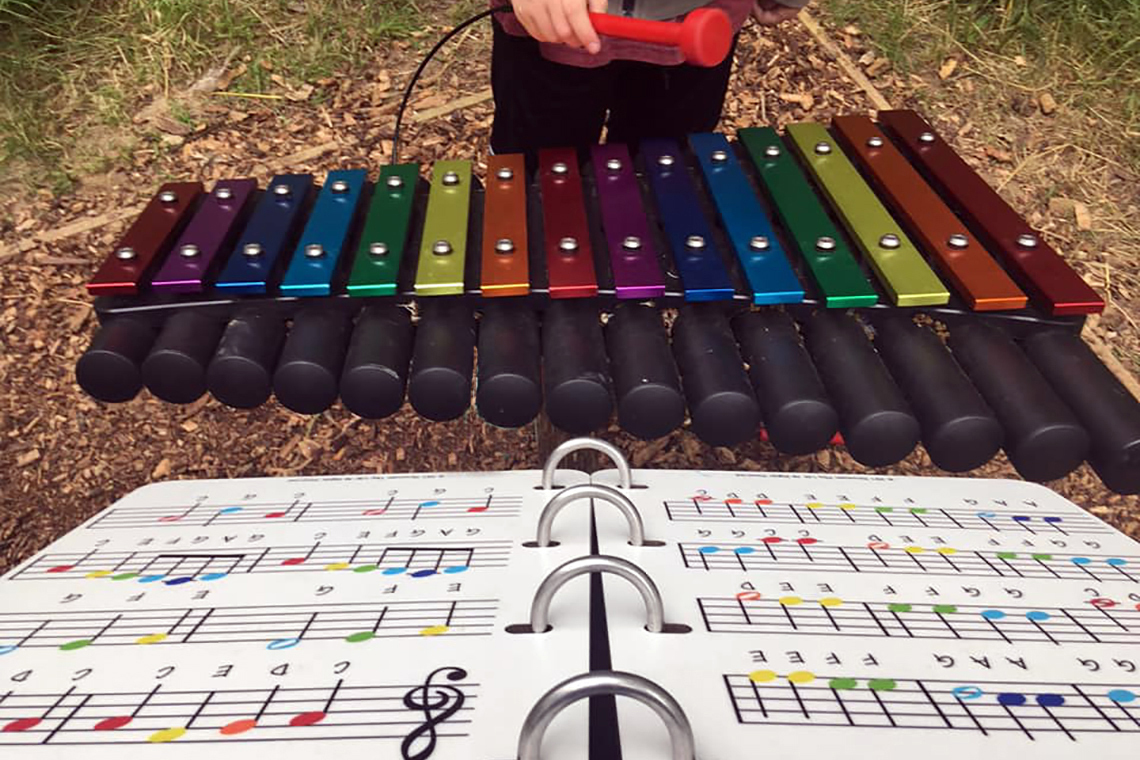 outdoor xylophone with rainbow coloured notes with accompanying music book with the notes colour match the xylophone