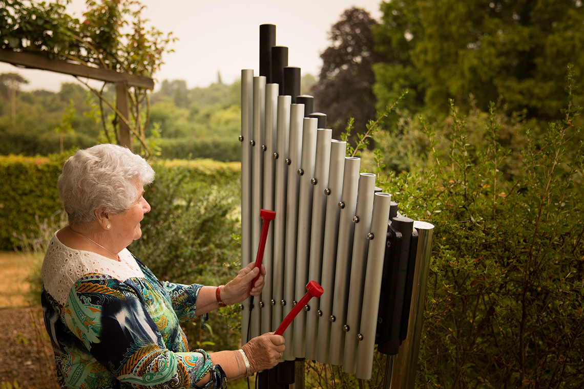 an older lady playing an upright outdoor xylophone in a care home garden
