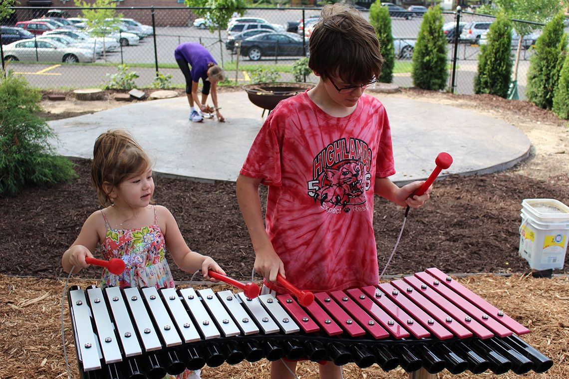 two children playing a large outdoor xylophone in playground