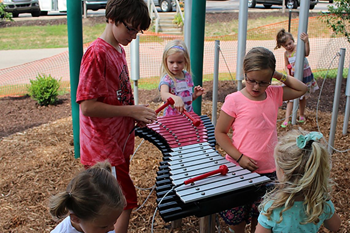 Group of children in a playground laughing and playing a large outdoor xylophone