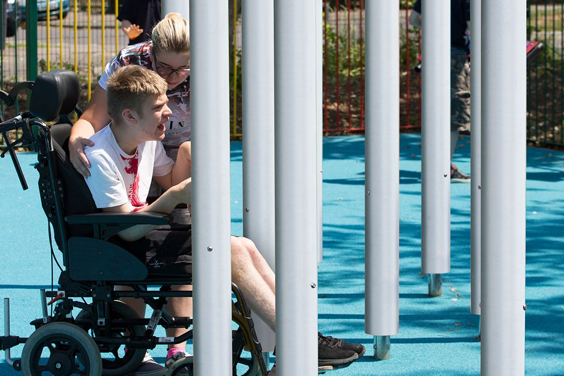 Young disabled man in a wheelchair with his carer playing on tall silver musical chimes in a school playground