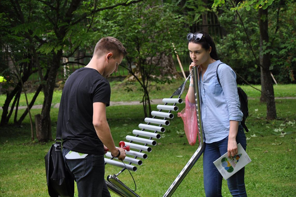 Young couple in a park playing a large outdoor musical instrument