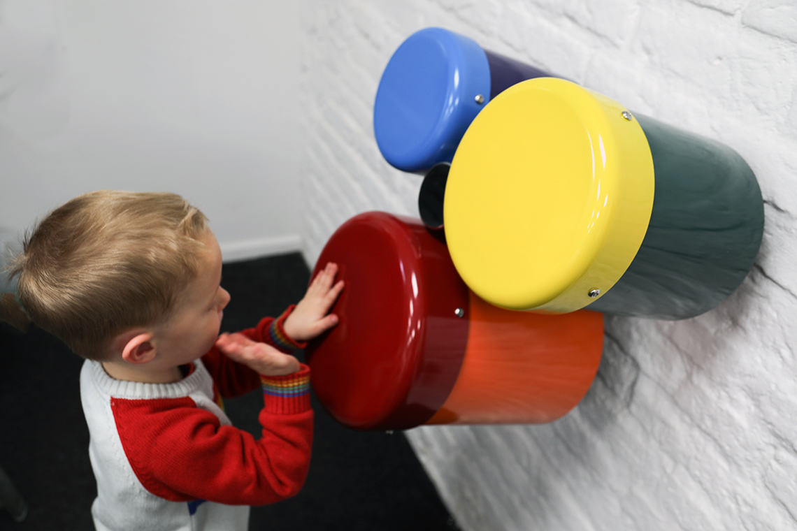 A group of three different sized wall mounted rainbow coloured outdoor bongo drums designed for smaller children