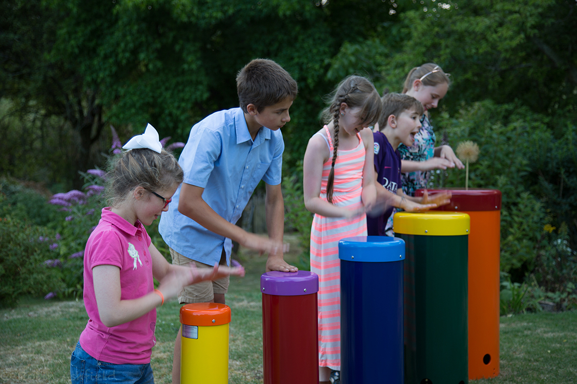 five children playing on a rainbow coloured set of samba drums in the outdoors