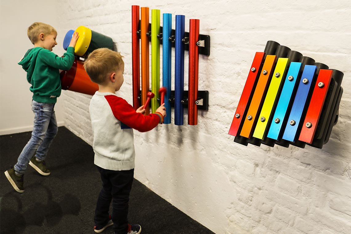 A collection of small outdoor musical instruments mounted on the wall suitable for nursery or kindergarten aged children