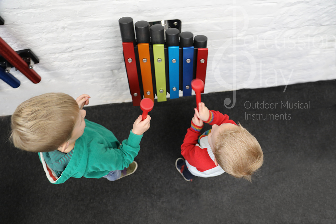 a small rainbow coloured outdoor metallophone for wall mounting suitable for nurseries and kindergartens