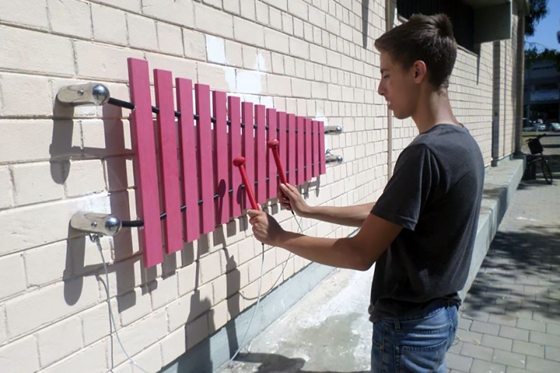 teenage boy playing a pink marimba mounted on a white wall in tel aviv