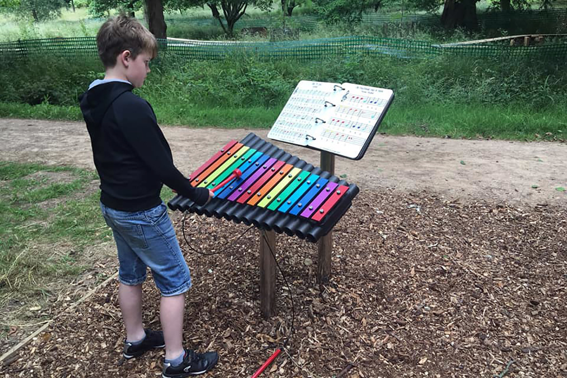an outdoor xylophone with rainbow coloured notes and an outdoor music book