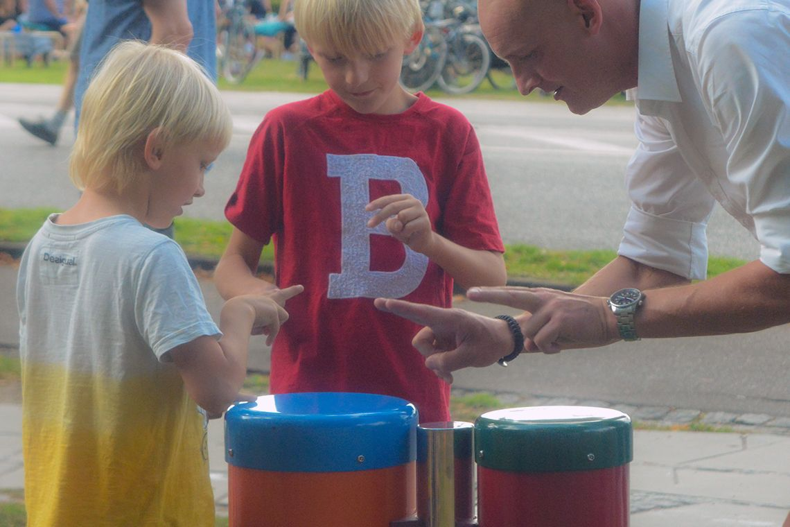 man with two boys plying conga drums in a playground